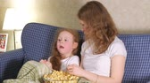 спальня : Happy loving family. Mother and her daughter child girl are eating popcorn on the bed in the room. front of the TV
