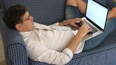 диван : Young man in glasses working remotely lying on sofa with laptop.close-up Стоковые видеозаписи