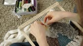 yarn : A woman weaves on a loom a beautiful embroidery made of yarn, in a home studio,