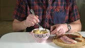 instante : The man is eating Chinese instant noodles with a fork