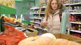 grocer : Woman buying cucumber and vegetables in delicatessen