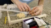 konular : A woman weaves on a loom a beautiful embroidery made of yarn, in a home studio,