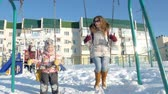 houpavý : Young mother with child swinging on swing set outdoor in winter park. Snow falling, snowfall , winter time Dostupné videozáznamy