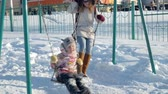 hinta : Young mother with child swinging on swing set outdoor in winter park. Snow falling, snowfall , winter time Stock mozgókép