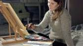 húz : Adult women paint with colored watercolor paints in an art school