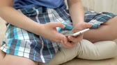 szófa : Teenager playing games on smartphone with excitement while sitting on floor at home