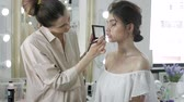 maskara : Young beautiful woman applying make-up by make-up artist