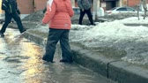 arranque : Girl in rubber boots jumping on puddle near wite paper boat