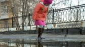 резина : Little beautiful girl jumping on puddles after rain Стоковые видеозаписи