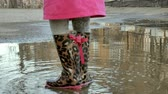 kir : Little beautiful girl jumping on puddles after rain Stok Video