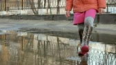 csomagtartó : Little beautiful girl jumping on puddles after rain Stock mozgókép