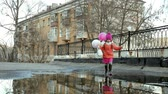 sevimli kız : Little beautiful girl jumping on puddles after rain Stok Video