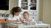 pequeno : Mother and child paint with colored fingers. Games with children affect the development of early children. Stock Footage