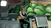 aeróbica : Young attractive woman enhancing her endurance while working out on an exercycle. portrait of a beautiful girl in the gym on a stationary bike. young woman on exercise bike aerobic exercise Stock Footage