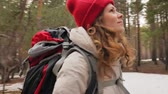 plecak : An attractive young woman in a red hat walks through the forest in early spring with a large tourist backpack
