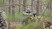 fegyveres : Soldiers in camouflage with combat weapons are being fired in the shelter of the forest, the military concept