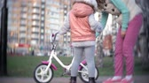 wsparcie : A laughing, smiling mother pushes her daughter forward on a warm spring day, when she teaches her to ride a bike along the citys sidewalk near a green park. Wideo