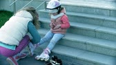 patenci : Mom and daughter ride on roller skates. Girl learning to roller skate, and falls. Mom teaches daughter to ride on rollers Stok Video