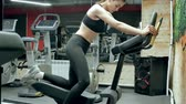 fino : An attractive woman does stretching on a simulator in a sports gym