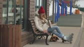 катание на коньках : Young beautiful woman in a red hat wearing sporty warm clothes and rollers, sitting on a wooden bench drinking tea from a bottle