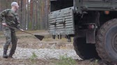 tehlikeli : Soldiers in camouflage with combat weapons in the forest near the battle car, military concept Stok Video