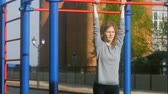coaching : young fitness woman doing exercises on the gym in an outdoor park