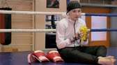 kickboxer : Woman kickboxer sits in the ring and drinks water after training