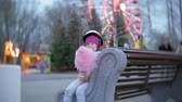 roller : Beautiful little girl sitting on a bench in an amusement park, eating pink sweet cotton candy rolling on roller skates