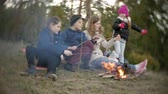 kids tent : Happy family of tourists on a journey. Mom and children fry marshmallows on the fire near the tent