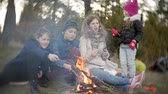 tenda : Happy family of tourists on a journey. Mom and children fry marshmallows on the fire near the tent