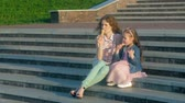 мороженое : Mom and daughter eating ice cream in a park. mother and child. relaxing happy family