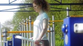 культурист : young fitness woman doing exercises on the gym in an outdoor park