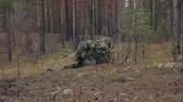 silahlı : Soldiers in camouflage with combat weapons are being fired in the shelter of the forest, the military concept