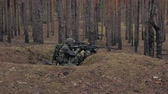 soldado : Soldiers in camouflage with combat weapons are being fired in the shelter of the forest, the military concept
