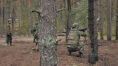 arma de fogo : Soldiers in camouflage with combat weapons are being fired in the shelter of the forest, the military concept