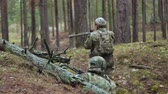 ser humano : Soldiers in camouflage with combat weapons are being fired in the shelter of the forest, the military concept