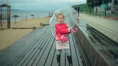 à prova d'água : Little beautiful girl with umbrella, playing in the rain, walking along the coast