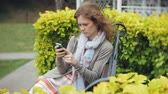 app : Woman Using Smartphone Relaxes on the Bench in Beautiful Green Park. Young Millennial Woman in Arboretum making gestures on Phone Display. Technology outdoors