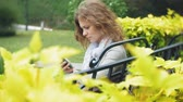 ławka : Woman Using Smartphone Relaxes on the Bench in Beautiful Green Park. Young Millennial Woman in Arboretum making gestures on Phone Display. Technology outdoors