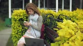 arboretum : Woman Using Smartphone Relaxes on the Bench in Beautiful Green Park. Young Millennial Woman in Arboretum making gestures on Phone Display. Technology outdoors
