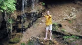 adversidade : young woman standing in front of waterfall with her hands raised. Female tourist with her arms outstretched looking at waterfall.