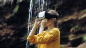 опыт : Girl virtual reality glasses VR sunny day wildlife woman raising hands peaks mountains, waterfall, forest electronic wearable technology using game simulator visual experience 3d cosmic innovation