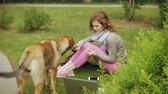 sem fio : A woman with a laptop relaxes on a grass lawn in a beautiful green park with her dog. A young perennial woman in an arboretum working behind a laptop. Technology in the open air