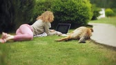 arboretum : A woman with a laptop relaxes on a grass lawn in a beautiful green park with her dog. A young perennial woman in an arboretum working behind a laptop. Technology in the open air