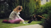 сотовый : A woman with a laptop relaxes on a grass lawn in a beautiful green park with her dog. A young perennial woman in an arboretum working behind a laptop. Technology in the open air