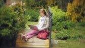 объектив : Woman with laptop relaxes on a bench in a beautiful green park. A young perennial woman in an arboretum working behind a laptop. Technology in the open air