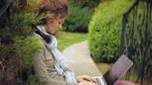arboretum : Woman with laptop relaxes on a bench in a beautiful green park. A young perennial woman in an arboretum working behind a laptop. Technology in the open air
