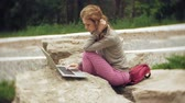 arboretum : A woman with a laptop relaxes on the rocks in a beautiful green park. A young perennial woman in an arboretum working behind a laptop. Technology in the open air