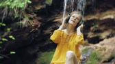 smartfon : young stylish beautiful woman, near a waterfall listening to music in large monitor headphones.