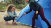 kids tent : Family of children and mothers gather a tourist tent on the bank of the river of the sea Stock Footage